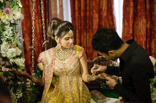 Indian bride applying mehendi